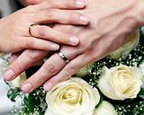 Closeup of newlywed holding hands over bouquet of flowers