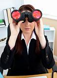 Radiant woman sitting on a chair in her office and looking through binoculars