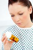 Caucasian female patient looking at pills