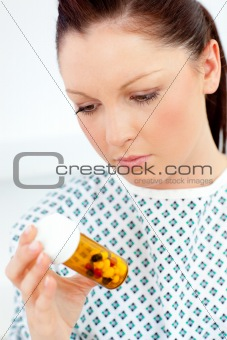 Caucasian female patient looking at pills
