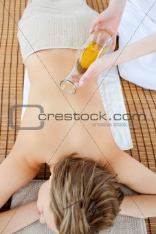 Beautiful woman having a massage with massage oil in a spa