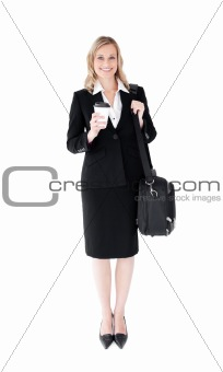 Smiling blond businesswoman holding coffee and a briefcase