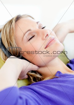 Relaxed woman listen to music lying on a sofa