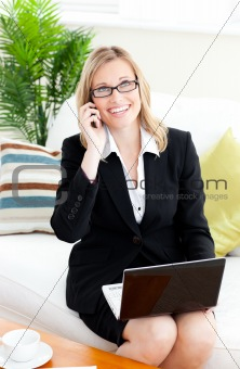 Ambitious businessowman talking on phone using her laptop
