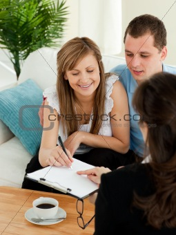 Bright young couple signing a contract sitting in their living r