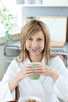 Charming woman drinking coffee in kitchen