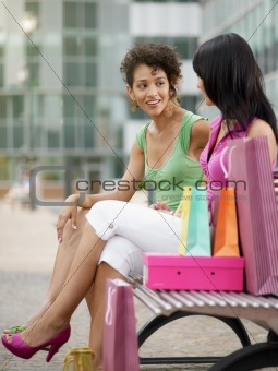 friends sitting on bench with shopping bags