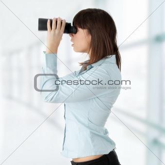 Business woman looking through binocular