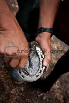 Close up of a man cleaning a horseshoe