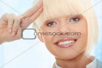 Attractive business woman saluting
