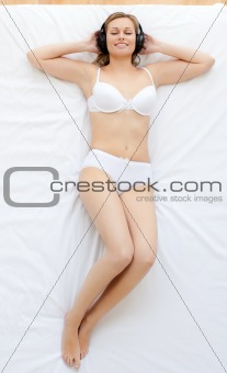 Positive woman listening to music in bed