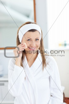 Charming woman putting cream on her face