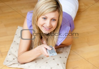 Blond woman watching TV holding a remote lying on the floor