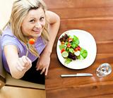 Blond woman eating a salad looking up to the camera