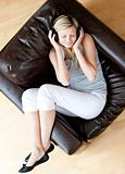 Relaxed woman listen to music with headphones sitting on a sofa