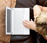 Beautiful woman using a laptop lying on a sofa