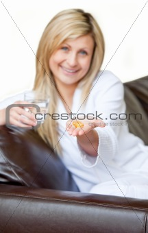 Happy woman holding pills and a glass of water smiling at the camera sitting on the sofa
