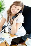Bright businesswoman talking on phone sitting in her office
