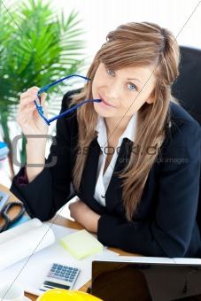Thougtful businesswoman holding glasses sitting at her desk
