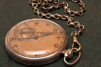 Old clock with chain lying on rough green surface