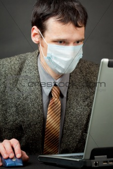 Man in medical mask works with laptop