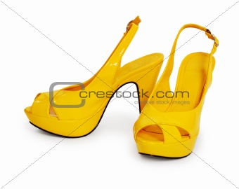 Pair of yellow female shoes isolated on white background