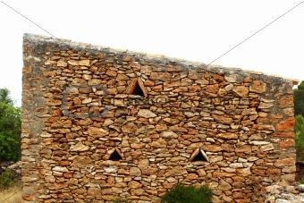 masonry stone wall triangle windows Formentera