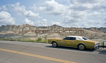 Old car driving in Badlands National Park