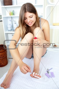Beautiful young woman doing a pedicure with red nail polish