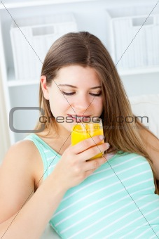 Caucasian young woman drinking orange juice