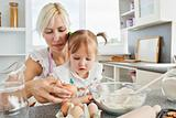 Focused woman baking cookies with her daughter