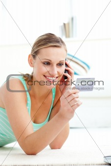 Charming young woman talking on phone holding a card