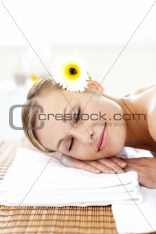 Blond young woman with flowers in her hair with closed eyes in a