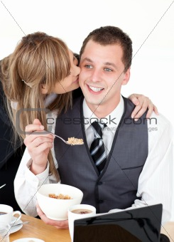 Beautiful blond businesswoman giving her smiling boyfriend a kis
