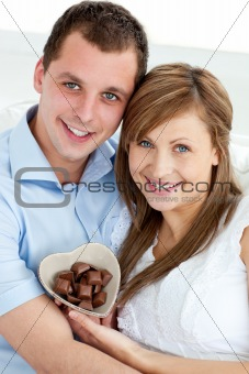 Hugging couple holding chocolote smiling at the camera
