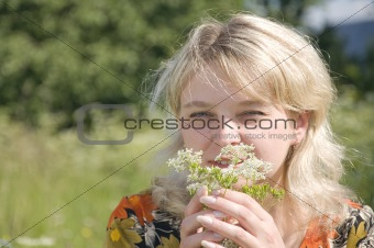 Beautiful girl in fresh grass smelling flower