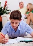 Young boy studying with family in the background