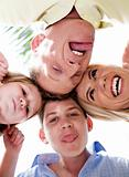 Joyful family making weird faces in huddle