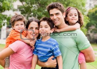Caucasian parents piggyback their children