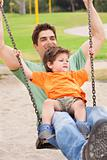 Father enjoying swing ride with his son