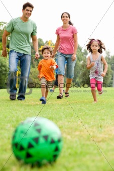 Family playing football in the park
