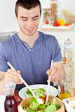 Attractive young man putting salad on a plate