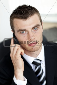 Assertive young businessman talking on phone looking at the came