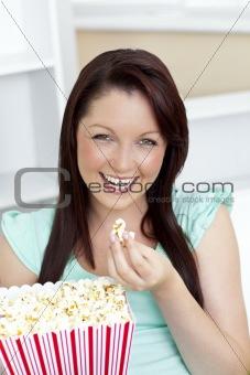Charming woman sitting on sofa with popcorn