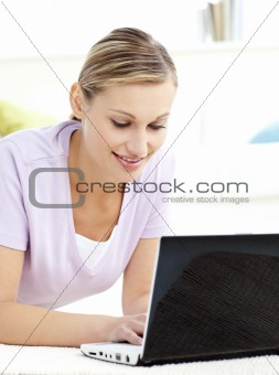 Attractive young woman using her laptop lying on the floor