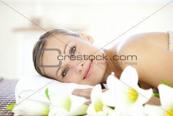 Charming woman lying on a massage table looking at the camera
