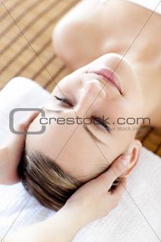 Positive blond woman receiving a head massage