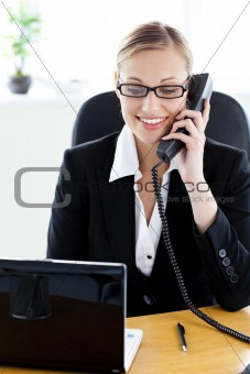Ambitious businesswoman talking on phone using her laptop