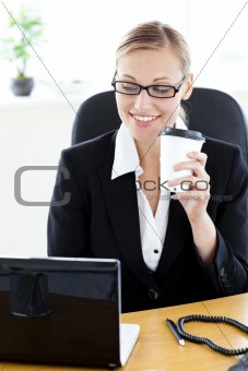 Positive caucasian businesswoman holding a coffee using her lapt