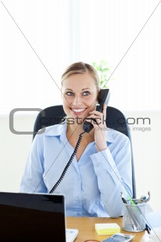 Charming young businesswoman talking on phone sitting at her des
